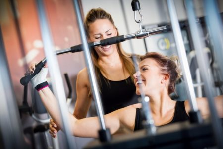 Personal trainer helps with gym equipment workout. Two attractive women training, building strength. Sport concept.
